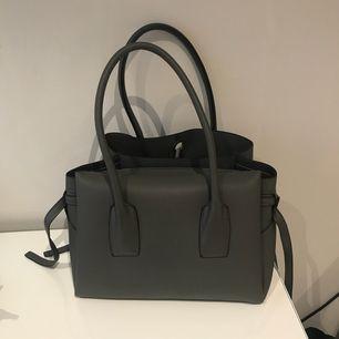 """En grå jättesnygg väska köpt på diabless! På sidorna har den avtagbara """"snören"""" och även en avtagbar axelrem! Den är endast använd ett fåtal gånger! Nypris:500"""