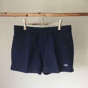 Stiliga marinblåa shorts från Adidas i kostymform. Storlek S-M, beroende på hur man vill att de ska sitta åt. Väl behållna!