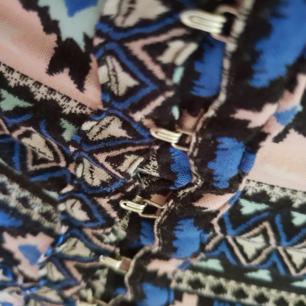 Lång mönstrad kjol från h&m. Knäppning i form av hylsor framtill på sidan, ganska hög slits. Alldeles för liten för mig så fick ej till någon bra bild. Kjolen är inte stretchig.