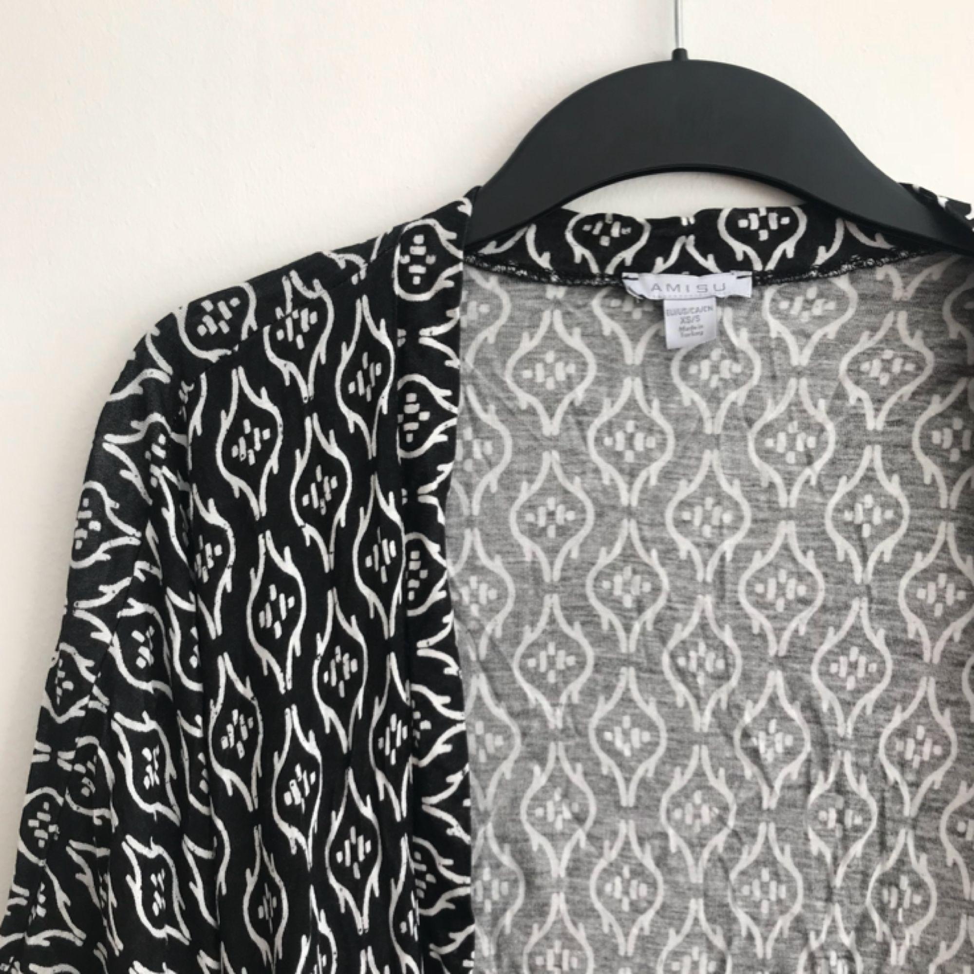 Jättefin svart/vit-mönstrad kaftan med fransar från New Yorker. Köparen står för frakten.. Tröjor & Koftor.