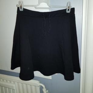 En svart kjol från barnavdelningen. Har knytband på framsidan.