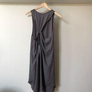 Grå klänning med ryggdetalj. Fint fall, funkar bra med ett bälte i midjan. Frakt inkluderat i priset 🌪🌫