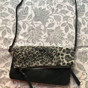 Väska med tunnt band, svart och grå leopardmönstrad.