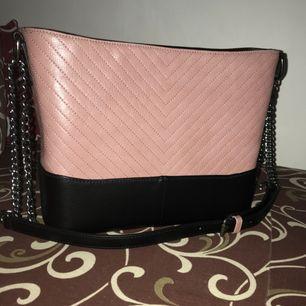 Säljer en oanvänd väska. Rosa med svart som ni ser på bilden väldigt fin. Säljer pga av att jag har andra väskor och denna väskan har inte kommit till användning. Finns dragkedja som på bilden med en innerfack.