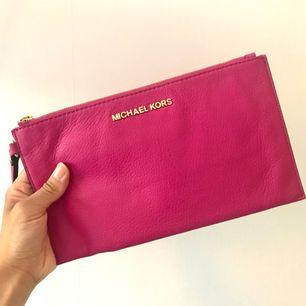 Äkta kuvertväska i cerise rosa från Michael Kors, köpt i New York för några år sen och har tyvärr inte kvittot kvar.   Massa innefack och sparsamt använd.  Mini fläck på baksidan från en bläckpenna.