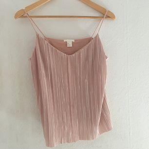 Plisserad rosa linne från H&M. Banden är sydda kortare än vad dem var när jag köpte linnet. Använd 1-2 ggr och passar S och M! Möts bara upp