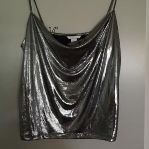 Metallic linne. Justerbar urringning och är i strl. S.