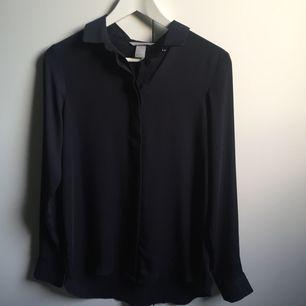 Tunn skjorta i mörkblått. Använd 1-2 gånger. Nyskick.
