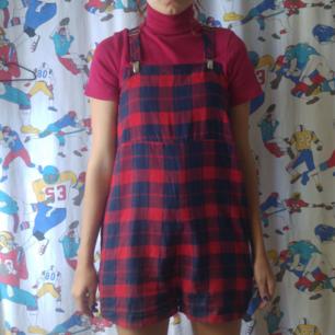 Supersöt hängselbyxa med shortsben. Röd och blårutig, från Asos i storlek 38 i tunt skönt material. Köparen står för frakten! Samfraktar gärna :)