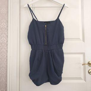 Fin blågrå shortsdress, reglerbar axelband, guldig dragkedja och fick på sidorna.