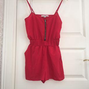 Fin röd shortsdress, reglerbar axelband, silver dragkedja och fickor på sidorna.