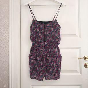 Fin blommig (lila,rosa,cerise och blå) shortsdress, reglerbar axelband, guldig dragkedja och fickor på sidorna.