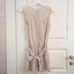 Beige shortsdress med band, stängs med knapar, spets upptill och fickor på sidorna.