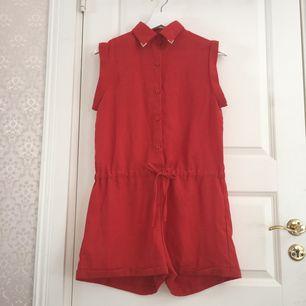 Orange/röd shortsdress med band, stängs med knappar, kragen har gulddetaljer och låtsas fickor på baksidan.