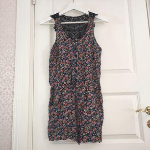 Blommig (lila, grön & orange) shortsdress, svart virkad bak, stängs med knappar och fickor på sidorna.