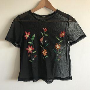 Söt topp med transparent tyg och broderade blommor, använd en gång.