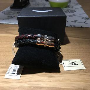 Två fina armband från GUL, armbanden är 21,5 cm och har ett spänne som är magnetiskt.   Nypris är 499kr/st, jag säljer båda för 500kr, aldrig använda, lapparna sitter kvar och kartongen är i bra skick.