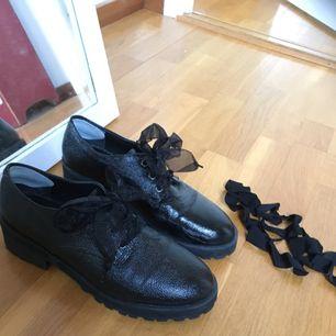 Glansiga skor med en låg klack och tjock sula. Två par snören - sidenband och vanliga svarta. 👢👠 Tillverkade i skinnimitation och kommer från Monki. Pyttelite slitna på insidan, vilket kan ses på bild tre.