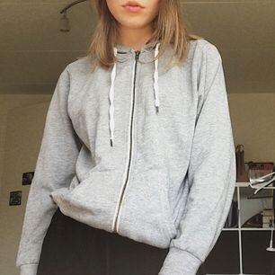 En jättefin basic grå hoodie med dragkedja, köpt second hand men har ändå behållts i bra kvalité! Passar perfekt nu till hösten eller till kyligare sommarkvällar :) Köparen står för frakt!. Huvtröjor & Träningströjor.