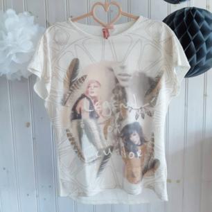 Beige t-shirt med tryck på framsidan från MillionX. Köpt i Europa-Center i Berlin. Sparsamt använd, i mycket bra skick. Strl 16 år (176 i barnstorlekar), men stor i storleken. Passar nog XS-M.   Har Swish! Köpare står för frakten!
