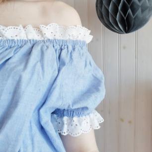 Ljusblå croppad off-shoulder-blus med vit spets och knappar. Köpt på secondhand, men i bra skick. Strl 38/40.
