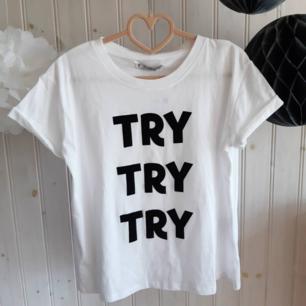 Ge inte upp! En vit t-shirt med svart slogantryck från Pull & Bear. I nyskick och helt oanvänd med lapparna kvar. Strl S.  (Nypris 129 kr).
