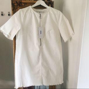 Vit jeansklänning med dragkedja framtill. Aldrig använd. Storlek 40 men passar bättre 36-38. Köpare står för frakt, betalas via swish.