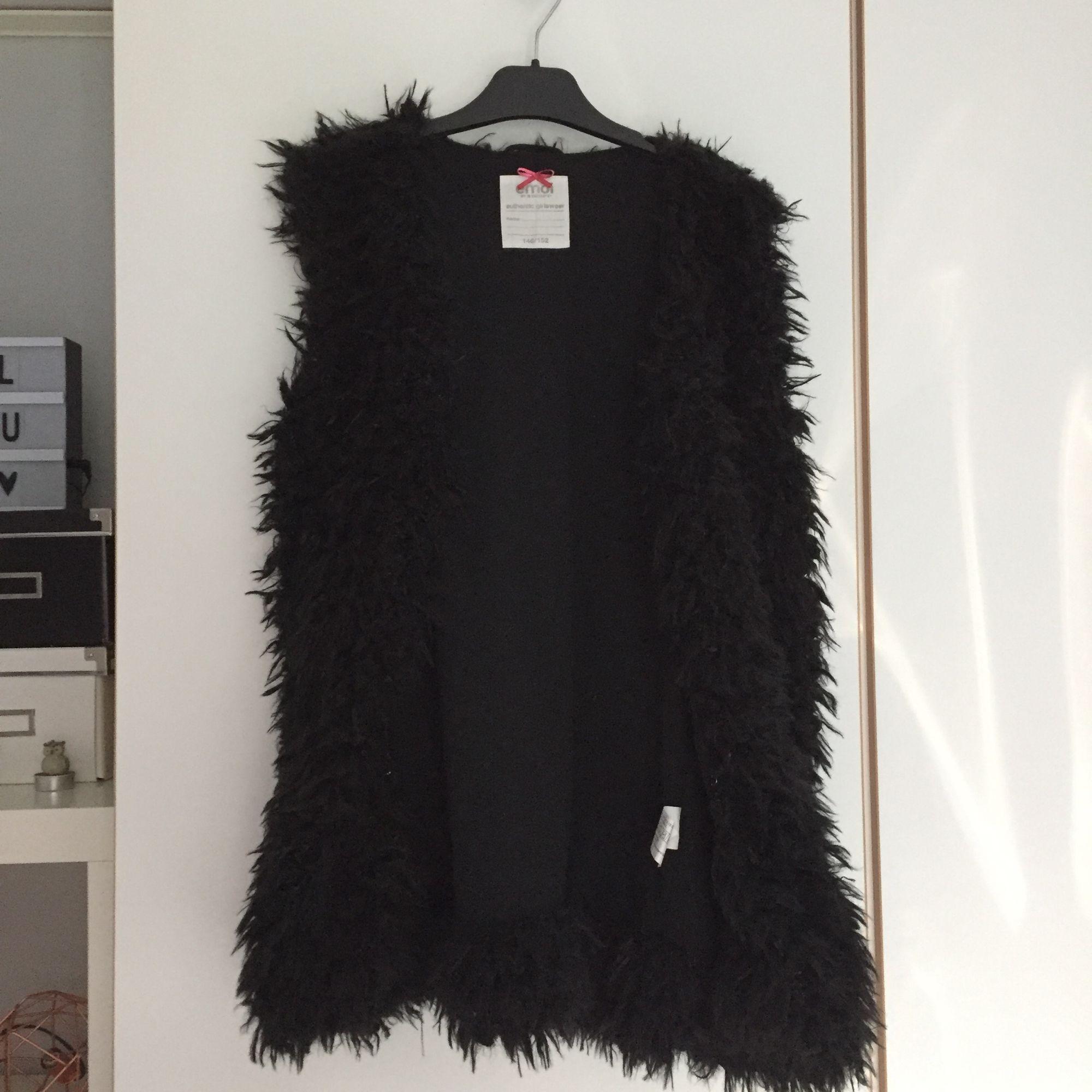En svart, fluffig, armlös kofta, använd en gång. Stl. 146/152 men passar som stl XS/S. Frakt betalas av köparen, betalning via swish.. Tröjor & Koftor.