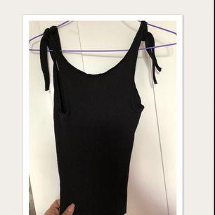 Svart oanvänt linne stretch med knytbara axelband