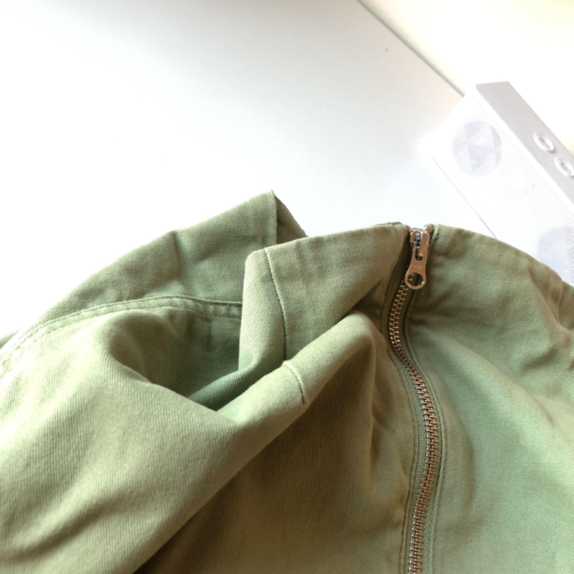 Grön kort kjol från Weekday, säljes pga för liten. Midjemått 64cm. Färgen stämmer bäst överens med sista bilden. Använd men inte sliten. Frakt inkluderad.. Kjolar.