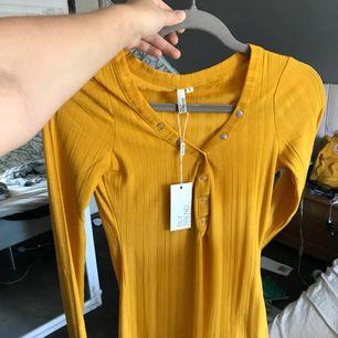 En helt ny gul tröja från Nelly. Är i storlek S, knappar som går att stänga och öppna.