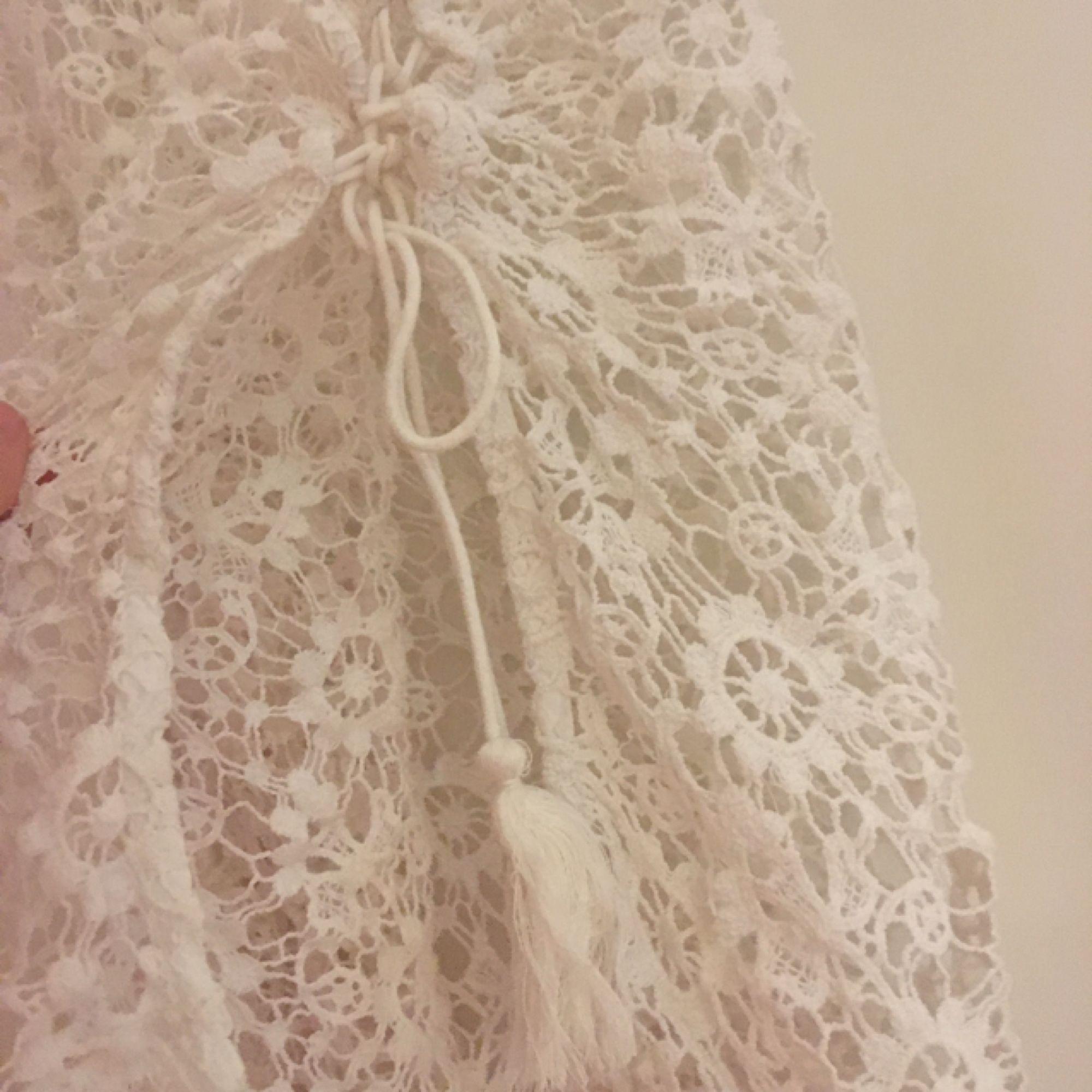 Ett strandigt vitt linne med knytning på båda sidor . Toppar.