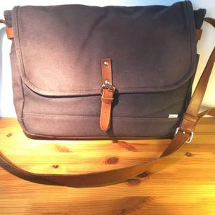 Sandqvist axelbandsväska. Rymmer laptop av standardstorlek. Mörkblå canvas med läderdetaljer. Använd och något solblekt.
