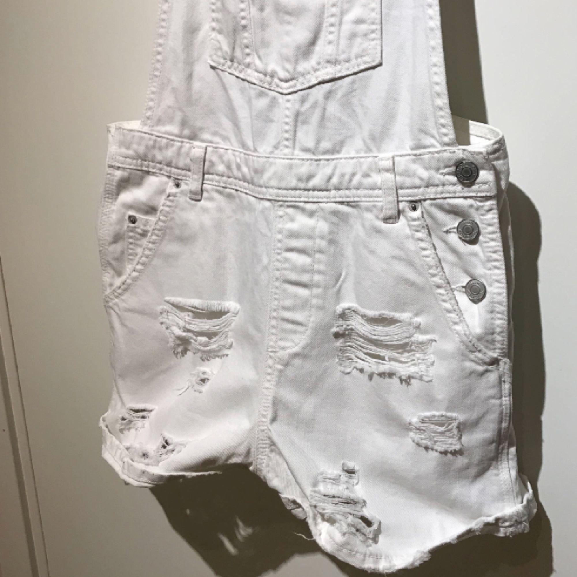 Vita hängselshorts från Topshop med slitningar. Plagget är i bra skick och säljs då den används alldeles för lite. Frakt ingår 😊. Jeans & Byxor.