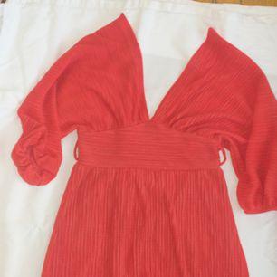 Korallfärgad plisserad klänning strl s m  Frakt tillkommer på 39kr