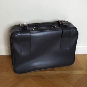 Vintage resväska i väldigt bra skick med fina detaljer. Spännen för att täcka stängning och justerbara band inuti. Avtagbar rem för adressdetalj. Fin till resa eller inredningsdetalj. Färgen återges bäst på detaljbilden.  Har Swish. Djur- & rökfritt hem.