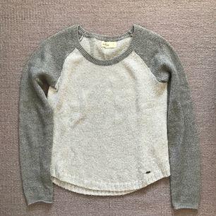 Grå stickad tröja från Hollister med silvertrådar i tyget. Använd fåtal ggr