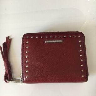 Plånbok från Rebecca Minkoff 100% läder. Färg skulle kalla oxblod. Knappt använd. Storlek relativt liten, får plats i handen som på andra bilden. Nypris ca 1100kr. Köpt på NK