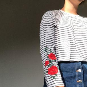 Så cool tröja från H&M med broderade rosor på ärmarna. Lite croppad, använd ett fåtal gånger så nyskick.  Köparen betalar frakt