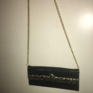 Jättecool, svart handväska med guldigt band och leopard-detalj.