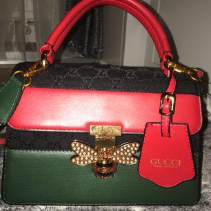 Säljer en Gucci väska väldigt fin och elegant. Axelrem medföljer och är justeringsbar. Kopia av riktiga
