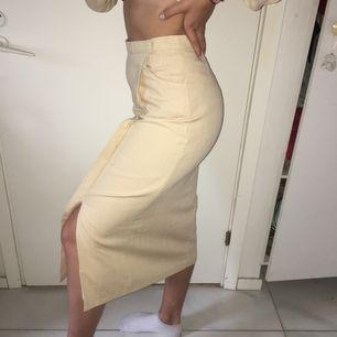 Lång beige-färgad kjol med cool passform. Sitter väldigt bekvämt och har slits på benet. Det står 34 i den men passar lätt någon som vanligtvis har stl 36.