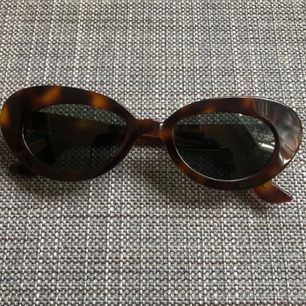 Fantastiskt fina solglasögon från franska varumärket Rouje. Brunmelerade bågar och mörkgrönt/gråaktigt glas. Ger 100% skydd mot stark sol utan att helt täcka ögonen. Inköpta i början av sommaren för 1400kr. Mycket gott skick!