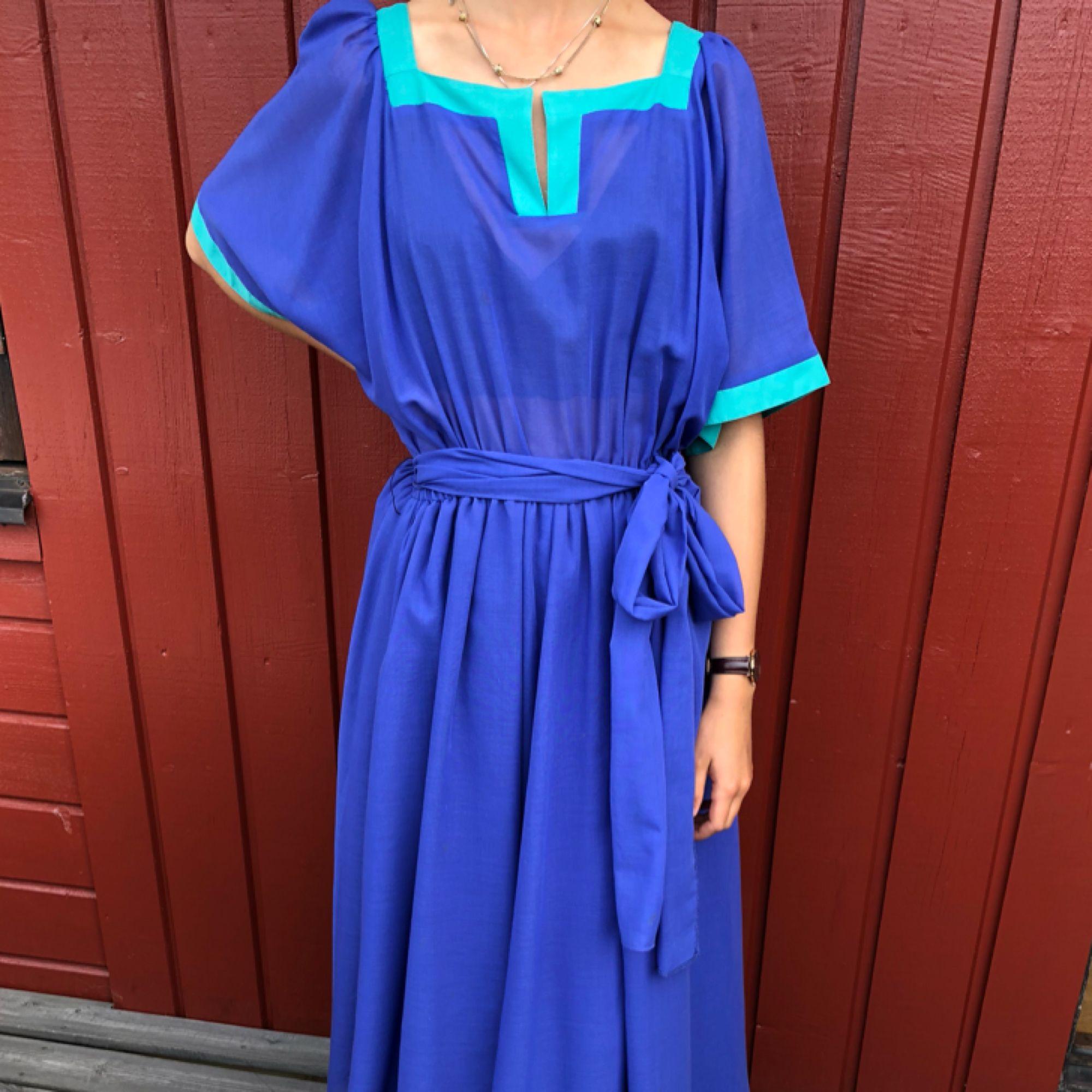 Klänning 50-tal i mörkblått svepande tyg.  Alla klänningar är i mycket fint skick! Modell är 172cm och S. Möts upp centrala Göteborg annars tillkommer frakt. . Klänningar.