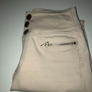 Högmidjade byxor i beige med gulddetaljer, bra begagnat skikt.