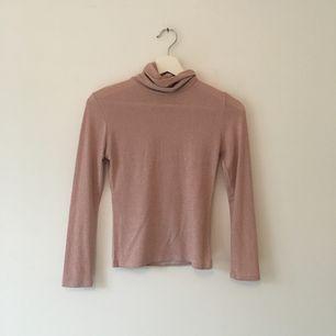 Fin glittrig rosa polotröja. Storlek står ej men funkar på XS och s. Den är i fint skick. Frakt ingår i priset:)