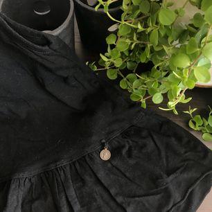 Ett svart linne som ändats använt 1 / 2 gånger, den har en volang ner till o knappt på baksidan - frakten ingår INTE i priset