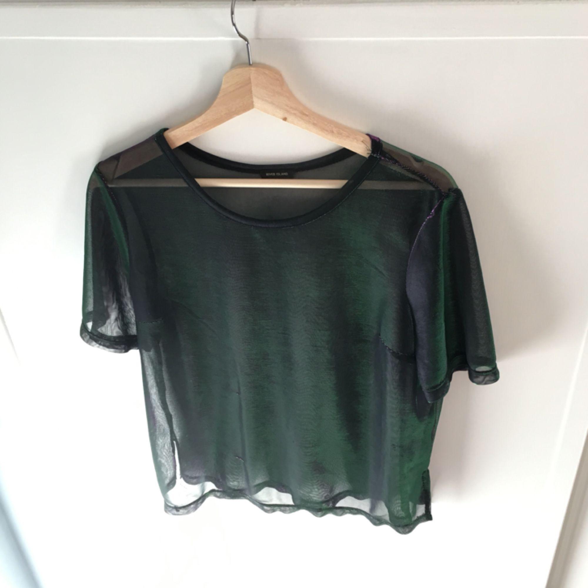 Cool skimrande t-shirt från River Island i mesh-tyg. Skimrar i lila och grönt beroende på vinkel. Sparsamt använd. Köpare står för ev frakt. . Toppar.