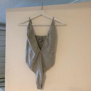 Grå bodysuit med fin urringning, köpt för ett antal år sedan men har sällan kommit till användning.   Finns att hämta upp i Stockholm alternativt fraktas mot en fraktkostnad. Från ett djur och rök-fritt hem.