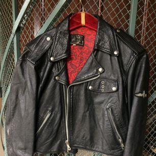 Skinnjacka i äkta läder från märket Vera Pelle, originalpris 1500kr. Den är i cropped modell med lite bredare axlar. Röd lining, två vanliga fickor samt en liten bröstficka